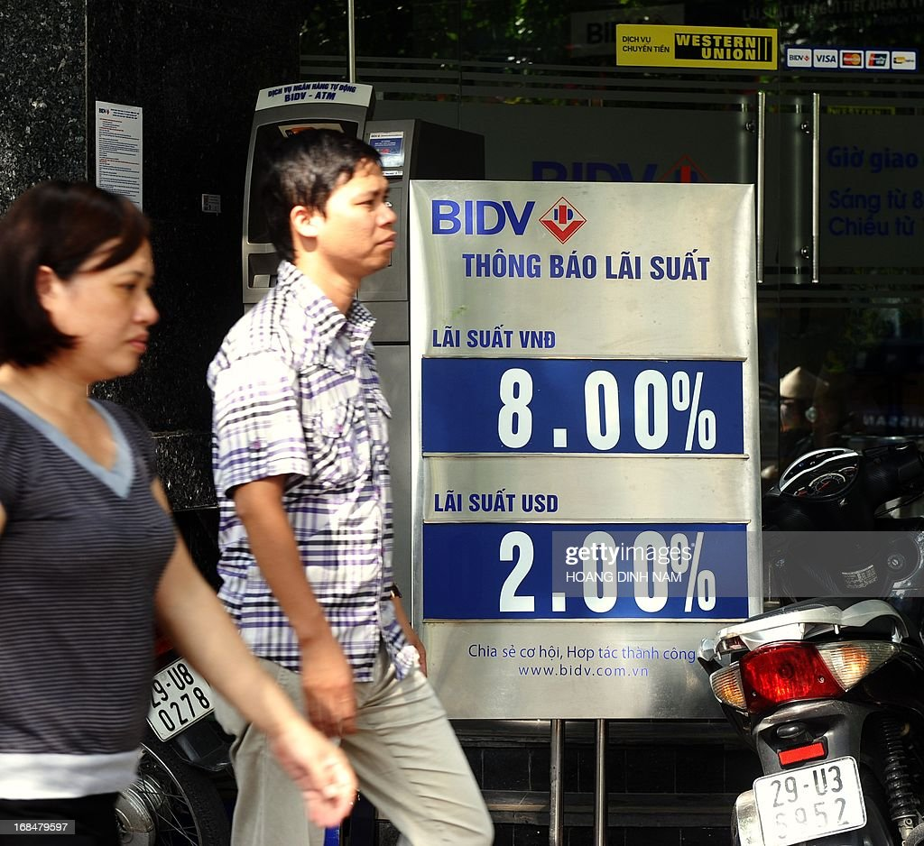 People walk past an outlet of the local commercial Bank for Investment and Development of Vietnam (BIDV) with saving interest rates offered for the local currency the dong (VND) at 8.00 % per year and US dollar at 2.00% per year in downtown Hanoi on May 10, 2013. Vietnam will cut interest rates for the eighth time in more than a year, hoping to improve the weakening economy, the central bank said on May 10. AFP PHOTO/HOANG DINH Nam.