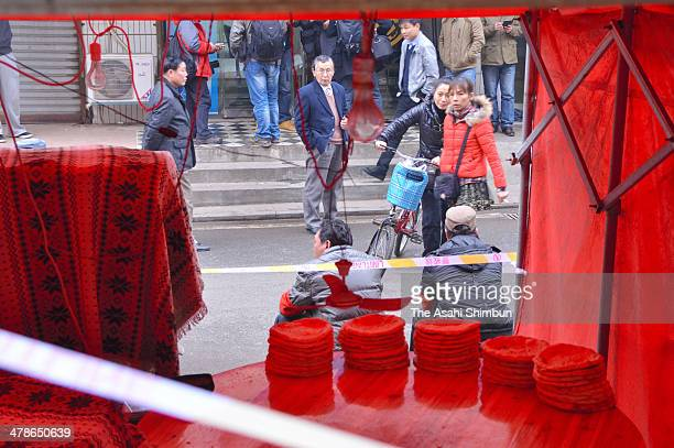 People walk past an Uighur naan stall the murder site of five people stabbed deadon March 14 2014 in Changsha Hunan China According to the residents...