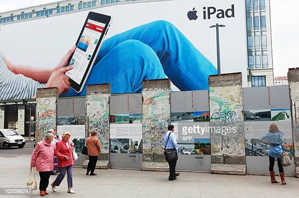 People walk past and look at a section of the Berlin Wall in front of a giant billboard featuring Apple's new iPad on June 15 2010 at Potsdamer Platz...