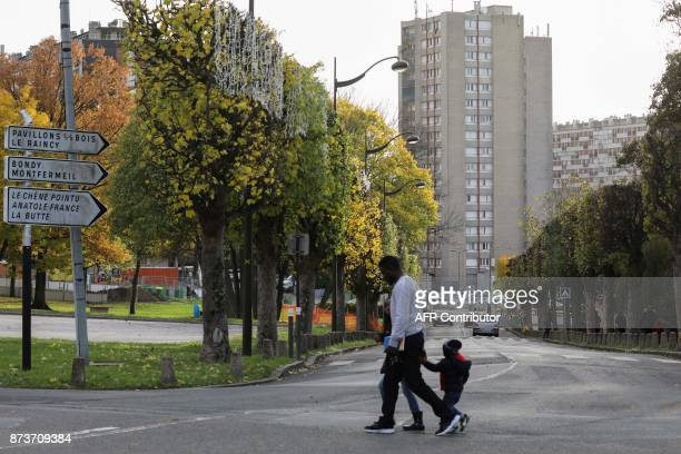 People walk past apartment buildings part of the Chene Pointu housing estate on November 13 in ClichysousBois northern Paris / AFP PHOTO / LUDOVIC...