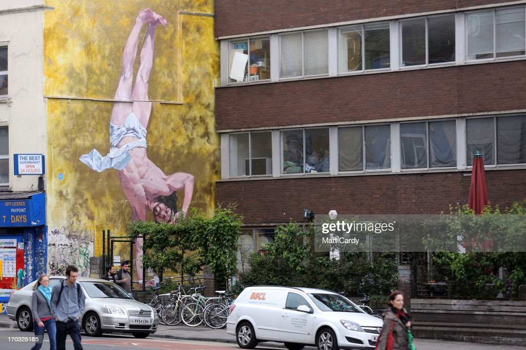 People walk past artist Cosmo Sarson's mural of Jesus breakdancing that he has painted on the 8.5 metre wall beside The Canteen in Stokes Croft and is being officially unveiled this evening is reflected in a window, on June 11, 2012 in Bristol, England. The artist was commissioned by The Canteen to paint the wall, which is directly opposite Banksy's Mild Mild West. The controversial 'Breakdancing Jesus', which took 4 days to paint and involved a kilo of glitter and was inspired by an actual event in the Vatican where breakdancers performed to an applauding Pope John Paul II in 2004, is likely to be the latest attraction for graffiti tourists visiting Bristol, often seen the spiritual home of underground artist Banksy.