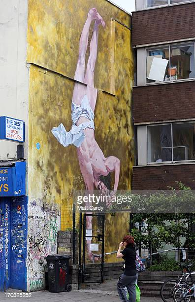 People walk past artist Cosmo Sarson's mural of Jesus breakdancing that he has painted on the 85 metre wall beside The Canteen in Stokes Croft and is...