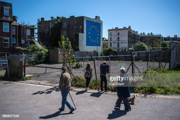 People walk past as a cameraman films a recently painted mural by British graffiti artist Banksy depicting a workman chipping away at one of the...