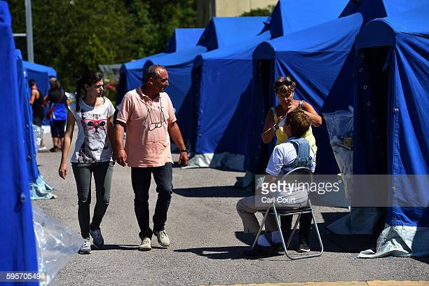 People walk past as a woman is treated for cuts and grazes to her face in a camp set up for people displaced by Wednesday's earthquake on August 26...