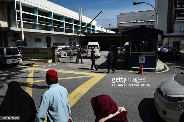 People walk past as Royal Malaysian policemen guard the forensics wing of the Hospital Kuala Lumpur where the body of Kim JongNam lies in Kuala...