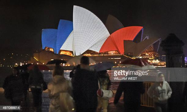 People walk past as the iconic sails of the Sydney Opera House are lit in red white and blue resembling the colours of the French flag in Sydney on...