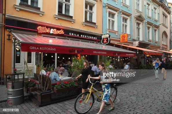 People walk past bars and restaurants in Kalku iela street in the old city center on May 19 2014 in Riga Latvia Founded in 1201 the city is a former...