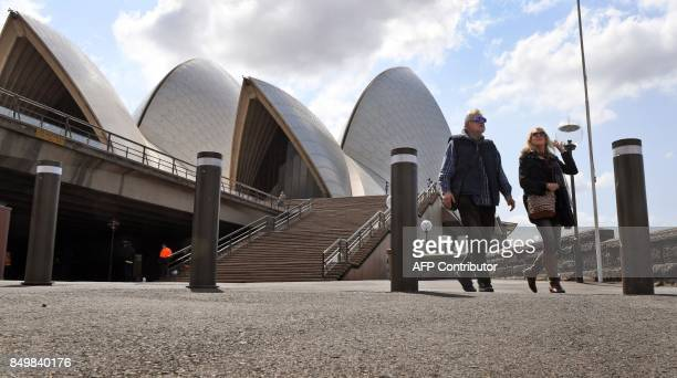 People walk past bollards installed to help protect tourists and locals from a terror attack at the Sydney Opera House on September 20 2017 A major...