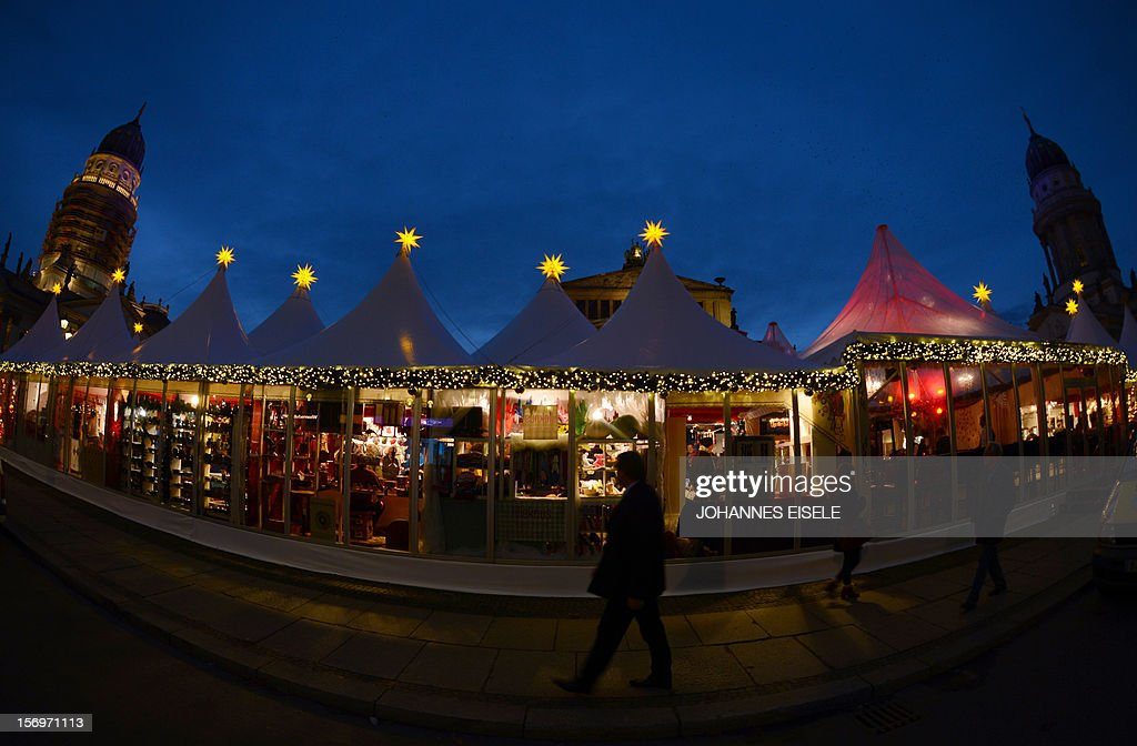 People walk past booths at Berlin's winter market at the Gendarmenmarkt after its official opening on November 26, 2012 in the German Capital. The market opens its doors from November 26 to December 31, 2012.
