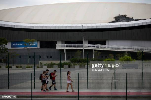 People walk past Brazil's Olympic velodrome in Rio de Janeiro Brazil on November 26 2017 The already damaged Olympic Velodrome caught fire overnight...