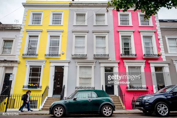 People walk past brightly poainted houses on Denbigh Terrace near Portobello Road Market in the Notting Hill district of west London on August 8 2017...
