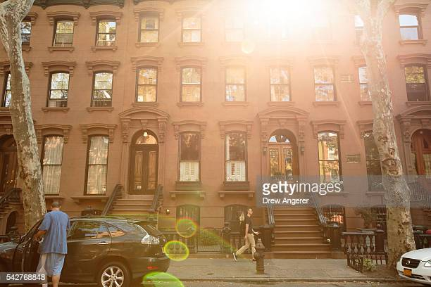 People walk past brownstone townhouses in the Fort Greene neighborhood on June 24 2016 in the Brooklyn borough of New York City According to a survey...