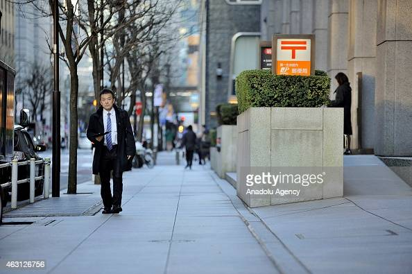 People walk past buildings of the financial and business of Tokyo Japan on February 10 2015 Japanese Prime Minister Shinzo Abe want to revitalise the...