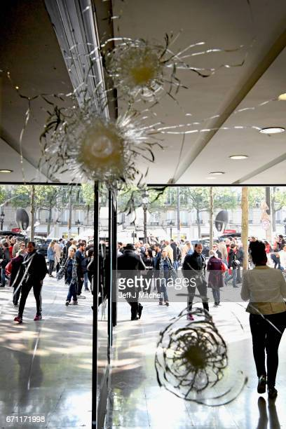 People walk past bullet holes in a window near to the Marks and Spencer on the Champs Elysees in Paris following yesterday's shooting of a police...