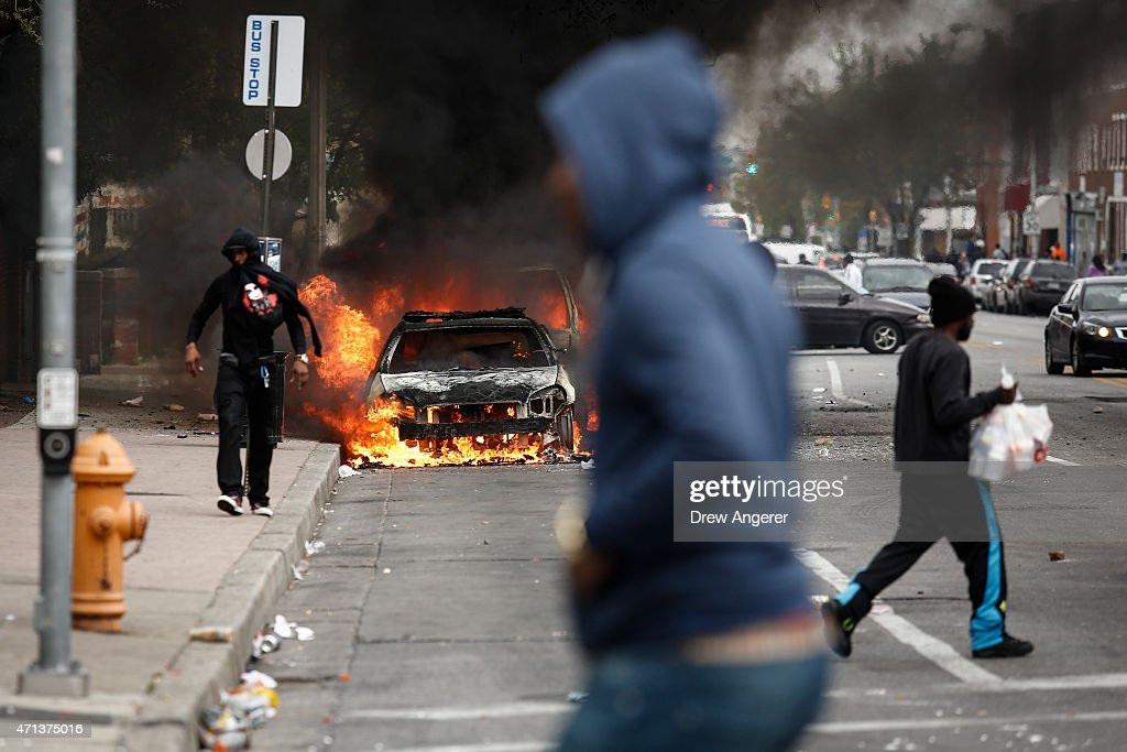 People walk past burning cars near the intersection of Pennsylvania Avenue and North Avenue April 27 2015 in Baltimore Maryland Riots have erupted in...