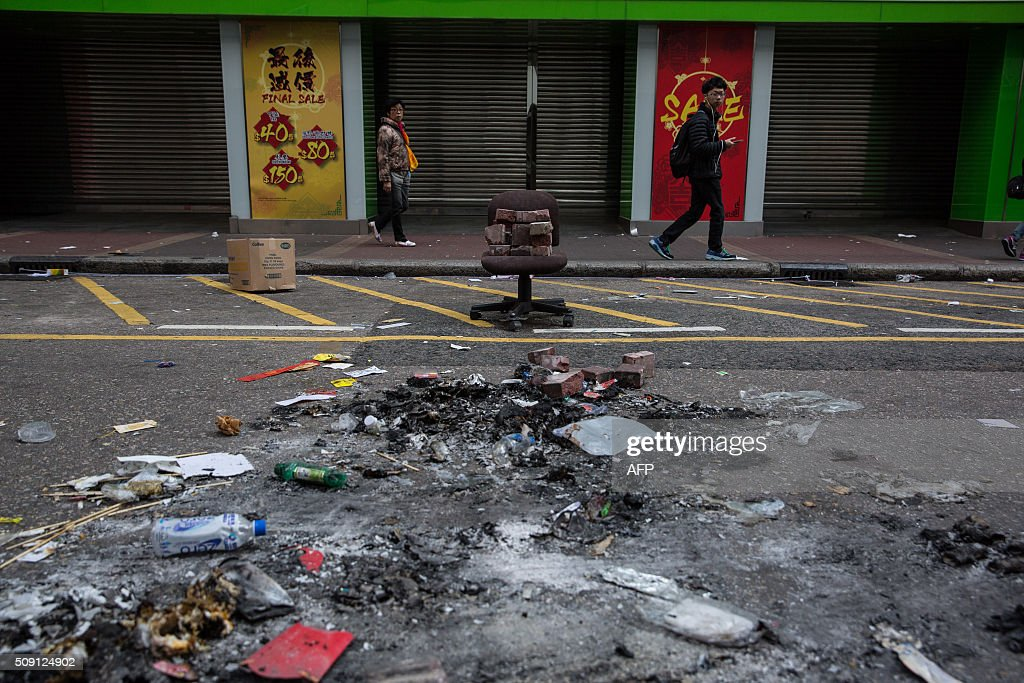 People walk past burnt debris scattered across the street following overnight clashes between protesters and police in the Mongkok area of Hong Kong on February 9, 2016. Baton-wielding Hong Kong riot police fired warning shots and tear gas early on February 9 after a riot erupted in the busy district of Mongkok when officials tried to shift illegal hawkers, local radio reported. AFP PHOTO / DALE DE LA REY / AFP / DALE de la REY