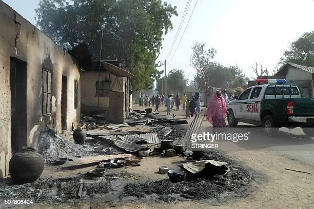 People walk past burnt houses after Boko Haram attacks at Dalori village on the outskirts of Maiduguri in northeastern Nigeria on January 31 2016...