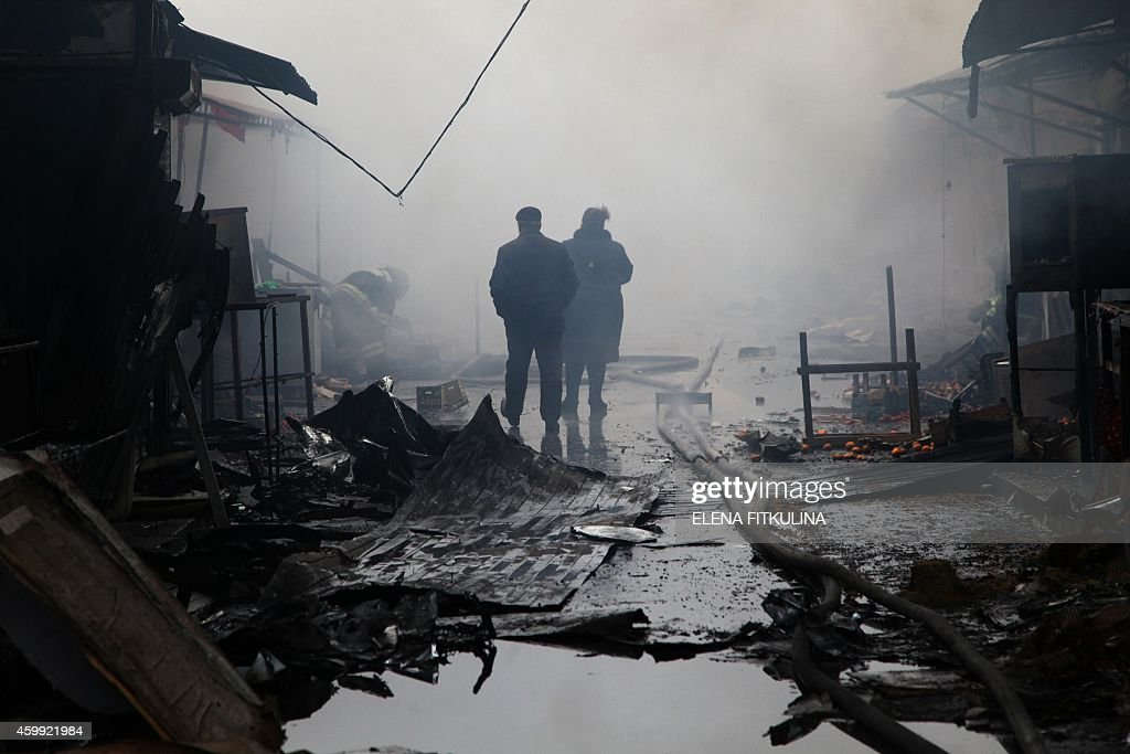 People walk past burnt out kiosks at a street market close to a destroyed building housing the housing the local media known as the Press House in...