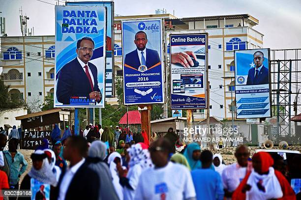 People walk past campaign posters of the forthcoming Somali presidential elections in Mogadishu Somalia on December 20 2016 The new Federal President...