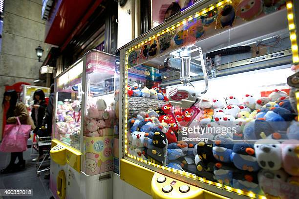 People walk past claw crane machines with stuffed animal toys outside a Taito Corp game arcade in Tokyo Japan on Thursday Dec 11 2014 Japanese stocks...