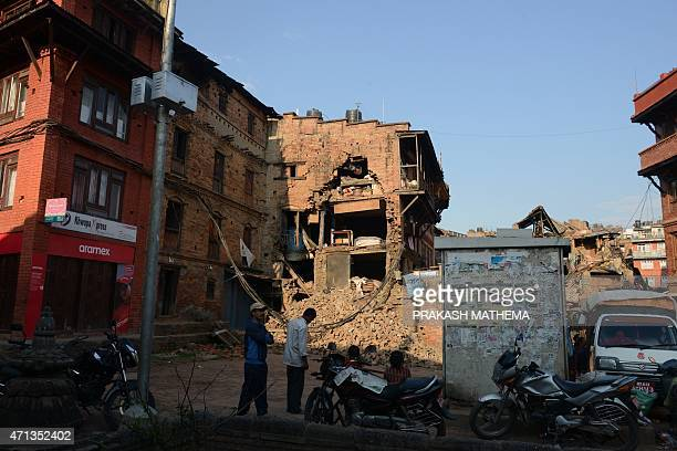 People walk past collapsed houses in Bhaktapur on the outskirts of Kathmandu on April 27 two days after a 78 magnitude earthquake hit Nepal Nepalis...