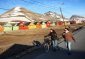 People walk past colourful cabins in the early morning of Midsummer on June 21 2008 in Longyearbyen Norway Longyearbyen is the seat of Norwegian...