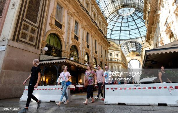 People walk past concrete barriers placed at the entrance of the Vittorio Emanuel II gallery close to the Duomo in Milan northern Italy on August 20...