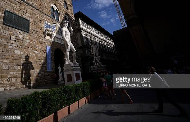 People walk past 'David' the famous sculpture by Italian artist Michelangelo at the Palazzo Vecchio Florence's town hall on May 20 2014 AFP PHOTO /...