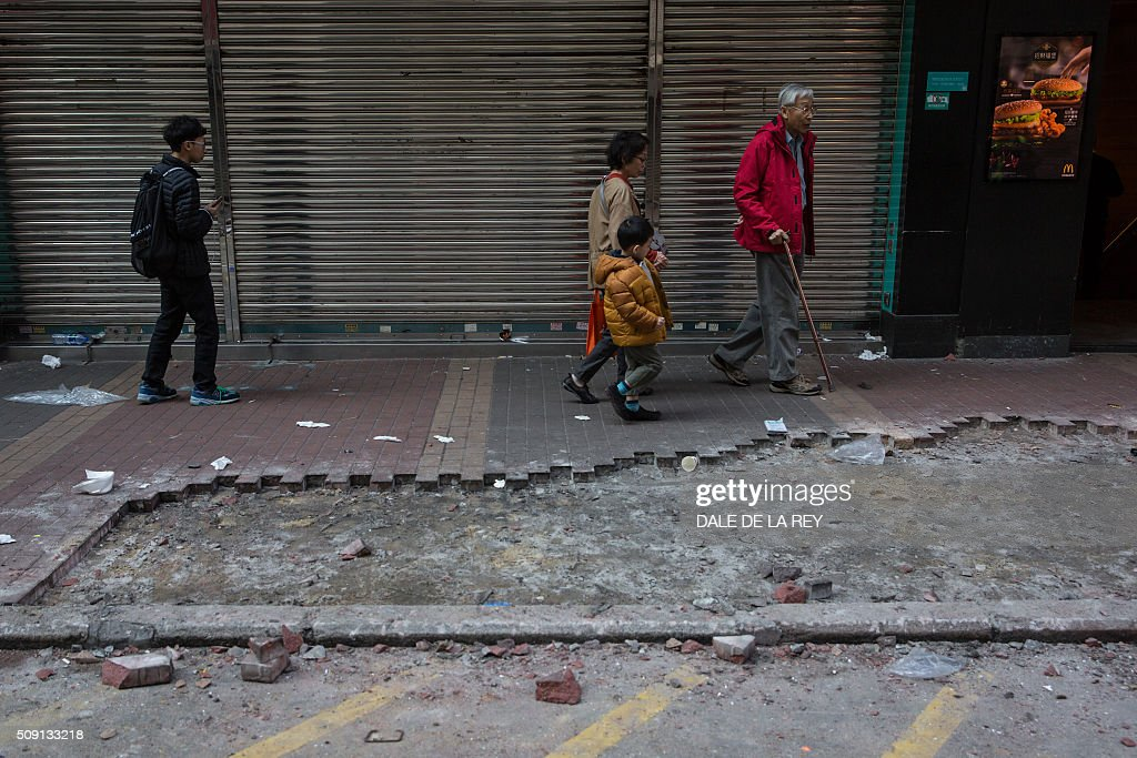 People walk past debris and a section of the pavement which was partial ripped up and used in overnight clashes between protesters and police in the Mongkok area of Hong Kong on February 9, 2016. Baton-wielding Hong Kong riot police fired warning shots and pepper spray early on February 9 after the riot erupted in the busy district when officials tried to shift illegal hawkers on Chinese New Year. AFP PHOTO / DALE DE LA REY / AFP / DALE de la REY