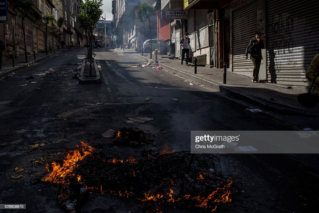 People walk past debris burning in the street after police dispersed protesters in the Okmeydani neighbourhood during a May Day demonstration on May 1, 2016 in Istanbul, Turkey. Turkish police used tear gas and water cannon to disperse protesters as they tried to make their way to Taksim Square.