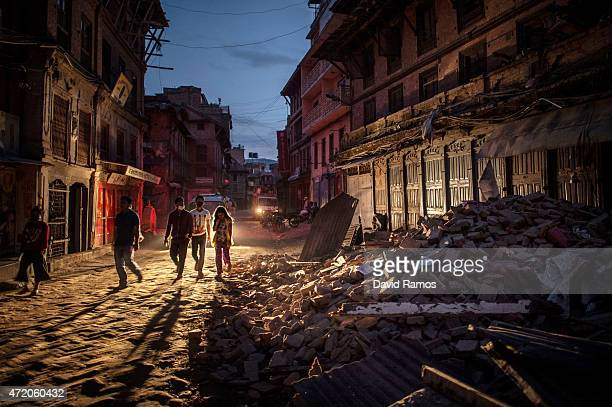 People walk past debris on May 3 2015 in Bhaktapur Nepal A major 78 earthquake hit Kathmandu midday on Saturday and was followed by multiple...