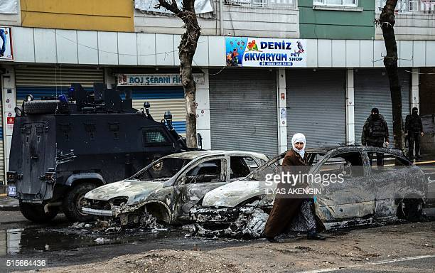 People walk past destroyed vehicles as they leave their houses during clashes in central Diyarbakir on March 15 2016 Turkish security forces clashed...