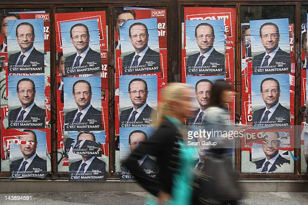 People walk past eleciton posters showing French Socialist presidential election candidate Francois Hollande in a street the day before the second...