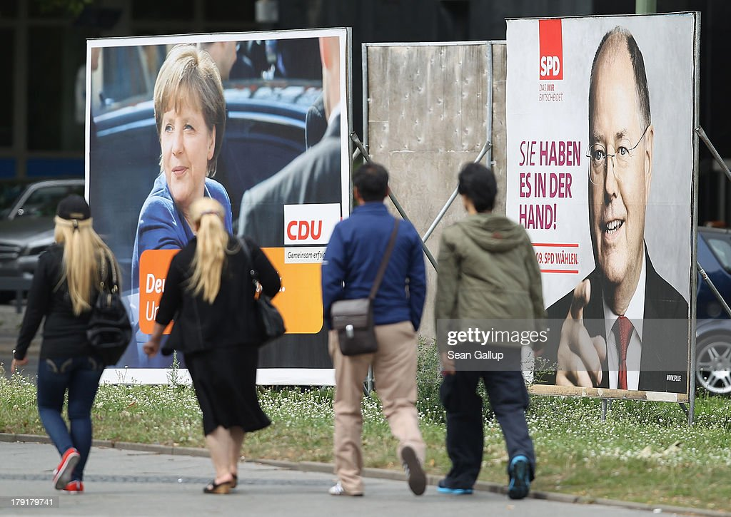 People walk past election campaign billboards featuring German Social Democrats (SPD) chancellor candidate Peer Steinbrueck (R) and German Chancellor and Christian Democrat (CDU) Angela Merkel on September 1, 2013 in Berlin, Germany. The two rivals are scheduled to face off in their first election television debate later today ahead of German elections cheduled for September 22.