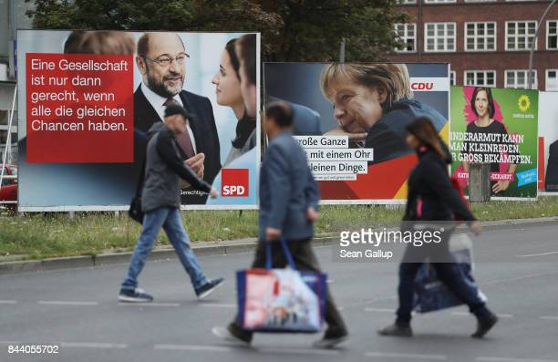 People walk past election campaign billboards that show German Social Democrat chancellor candidate Martin Schulz German Chancellor and Christian...