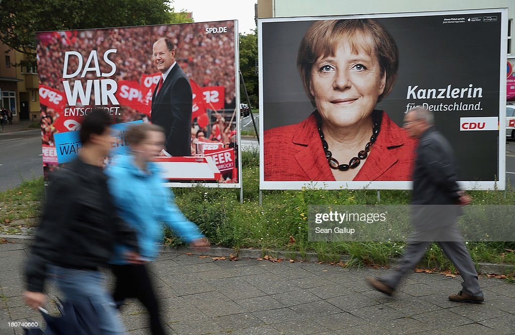 People walk past election campaign posters featuring German Chancellor and Chairwoman of the German Christian Democrats (CDU) Angela Merkel (R) and German Social Democrats (SPD) chancellor candidate Peer Steinbrueck on September 16, 2013 in Berlin, Germany. Germany faces federal elections on September 22 and so far the CDU has a strong lead in polls over the SPD, its biggest rival, and other members of the opposition.