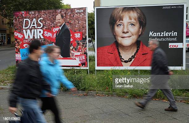 People walk past election campaign posters featuring German Chancellor and Chairwoman of the German Christian Democrats Angela Merkel and German...