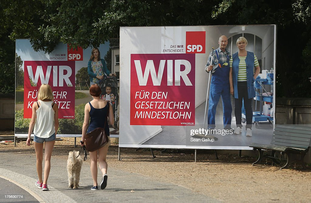 People walk past election campaign posters of the German Social Democrats (SPD), including one (R) that reads: 'We, for the compulsory minimum wage,' in the city center on August 6, 2013 in Berlin, Germany. Germany is scheduled to hold federal elections on September 22 and so far current Chancellor Angela Merkel and her party, the German Christian Democrats (CDU), have a strong lead over the opposition.