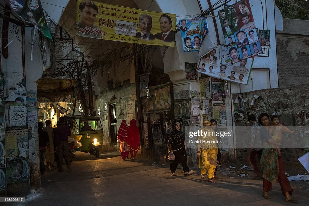 People walk past election campaign posters the day after election day on May 12, 2013 in the Old City of Lahore, Pakistan. The electoral committee recorded a high voter turn out as millions of Pakistanis cast their votes in yesterdays parliamentary elections. It is the first time in the country's history that an elected government will hand over power to another elected government. Initial results show the PML-N party has recorded the highest number of seats won and party leader.Nawaz Sharif has claimed victory ahead of the last official results.