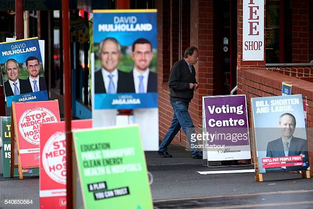 People walk past electoral placards featuring photos of Bill Shorten Leader of the Australian Labor Party and Malcolm Turnbull Leader of the Liberal...