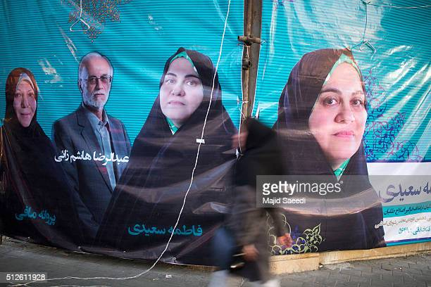 People walk past electoral posters in downtown on February 25 2016 in Tehran Iran Iranians voted on Friday in parliamentary elections the country's...