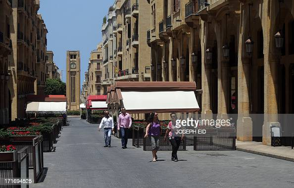 People walk past empty restaurants in downtown Beirut which was once crowded by tourists mainly from the Gulf states at this time of the year on June...