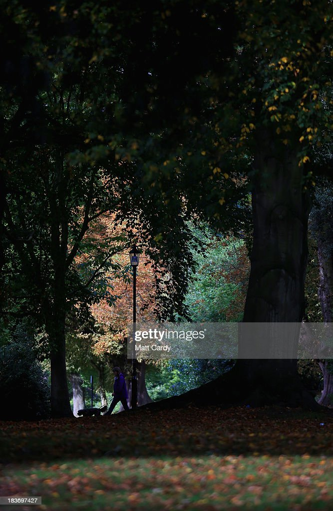 People walk past fallen leaves as the trees begin to take on their autumn colours in The Royal Victoria Park on October 9, 2013 in Bath, England. Although later than normal, experts at the Forestry Commission are predicting a spectacular autumn this year due to a ideal mix of sunshine and rain which has meant a great growing season for the nations trees, providing perfect conditions for the sugars to build up in the leaves that help them change colour and develop their vibrant autumn hues.