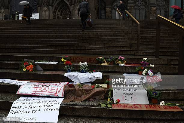 People walk past flowers and letters of protest that are laid down on the steps of the Cathedral in front of the Cologne main train station in...
