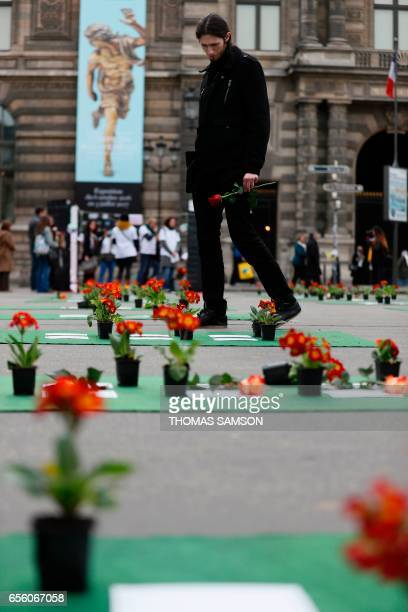 People walk past flowers laid by members of the group 'les Morts de la Rue' on the Place du Palais Royal in Paris on March 21 in memory of 501...