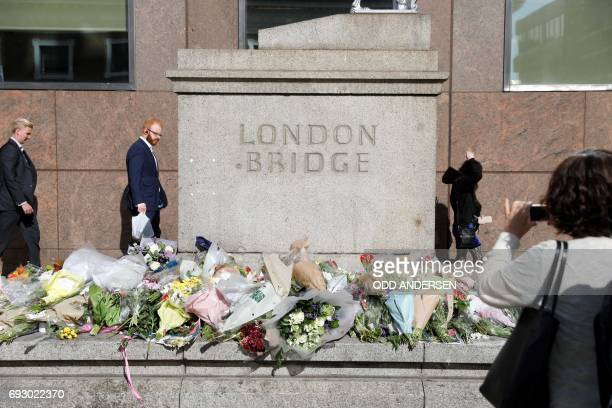 People walk past flowers layed south of London Bridge in London on June 6 for the victims of the June 3 terror attack on the bridge and at Borough...