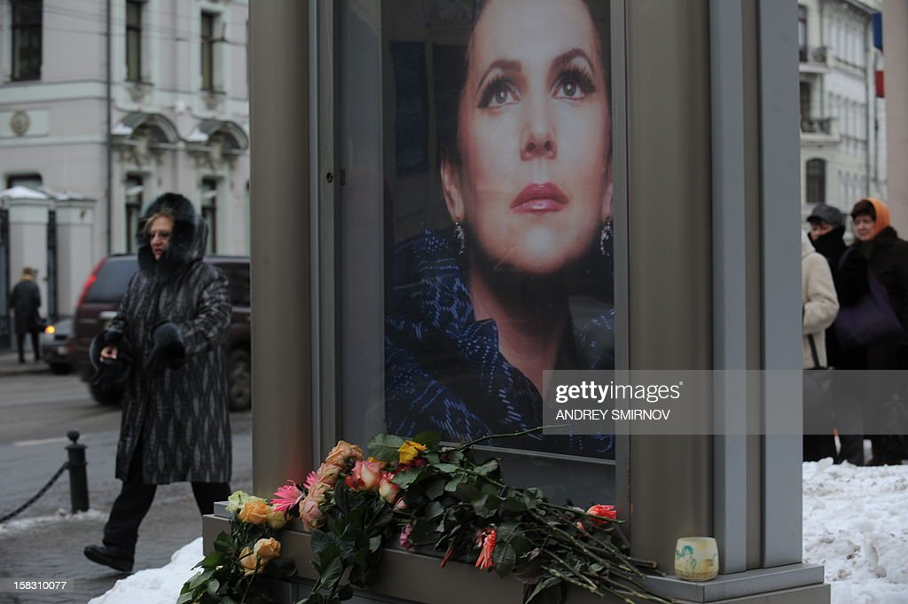 People walk past flowers lying at a portrait of opera singer Galina Vishnevskaya just outside the opera singing center founded by the soprano in Moscow, on December 13, 2012. Vishnevskaya, the widow of legendary cellist Mstislav Rostropovich who is known for her iconic interpretations of great opera roles, died at 86.