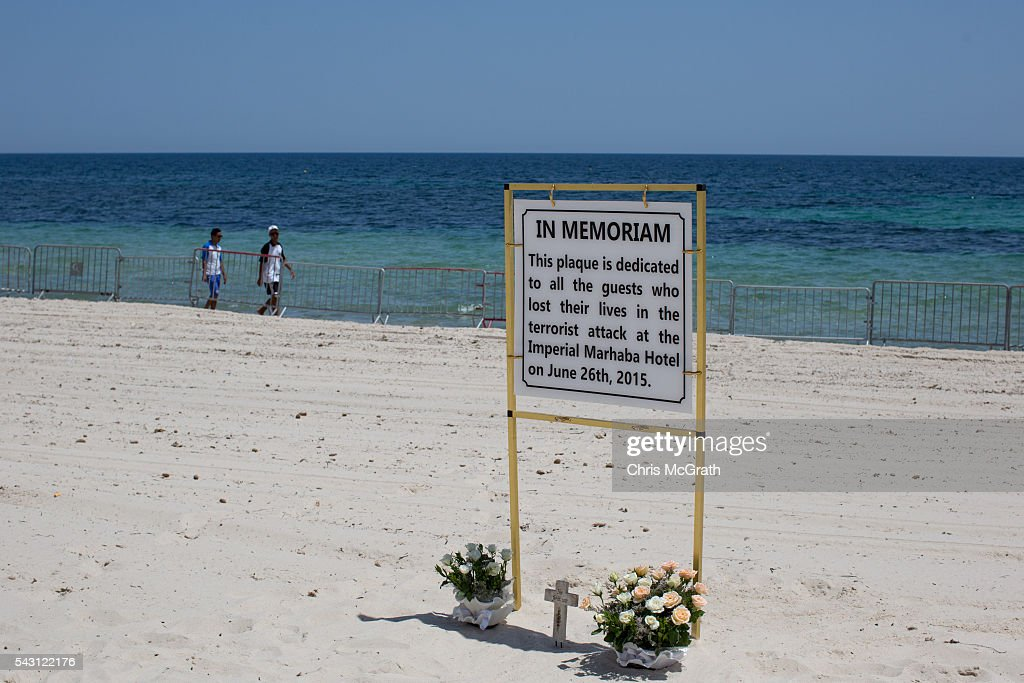 People walk past flowers placed by tourists underneath a memorial sign on the beach in front of the Imperial Marhaba hotel on June 26, 2016 in Sousse, Tunisia. Today marks the one year anniversary of the Sousse Beach terrorist attack, which killed 38 people including 30 Britons. Before the 2011 revolution, tourism in Tunisia accounted for approximately 7% of the country's GDP. The two 2015 terrorist attacks at the Bardo Museum and Sousse Beach saw tourism numbers plummet even further forcing hotels to close and many tourism and hospitality workers to lose their jobs.