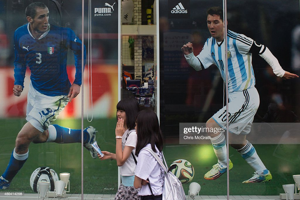 People walk past football posters on display at a retail store on June 11, 2014 in Tokyo, Japan. The World Cup 2014 in Brazil will begin on June 12th with the first match between Brazil and Croatia.