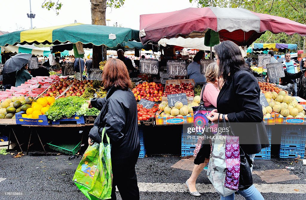 People walk past fruit and vegetable stalls at a market in Lille, on August 18, 2013. While several organizations are denouncing the rise in the price of fruits and vegetables this summer by over 14% to 17%, a major farmers union from the Lot-et-Garonne region is preparing to sell fruits and vegetables directly to consumers in Paris and surrounding cities at a 'fair price' to protest against the excessive profit margins of large scale retail and stores which they say make it impossible for them to earn a fair amount for their produce. AFP PHOTO / PHILIPPE HUGUEN